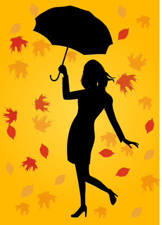 autumn woman: silhouette of woman in autumn coat holding an umbrella under fall of the leaves