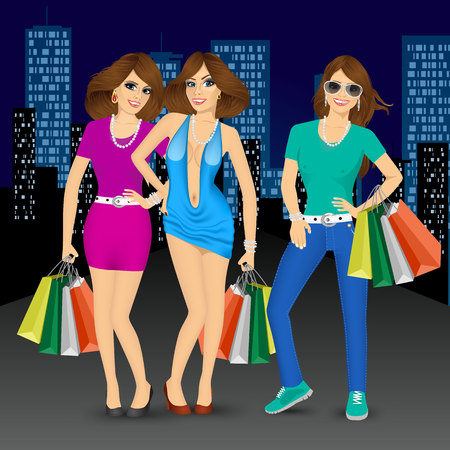 group of young smiling pretty women holding shopping bags standing in night city