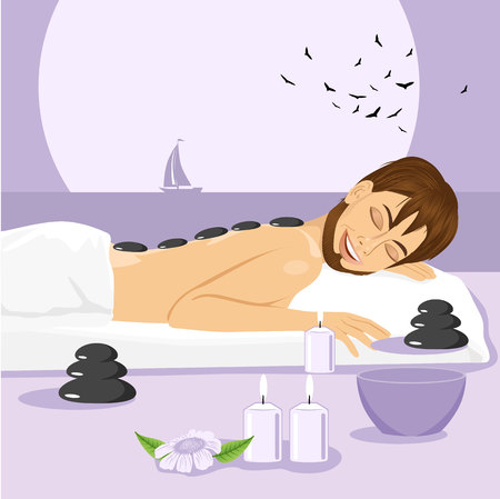 man lying down: Handsome man having stone massage in spa salon. Healthy lifestyle