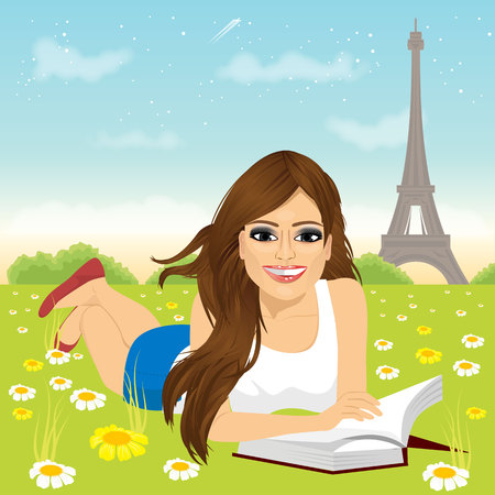 woman lying down: attractive brunette latina woman lying down on grass reading book in the peaceful park in Paris.