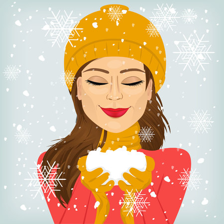 woman in scarf: attractive brunette woman with eyes closed and smiling in yellow winter hat and scarf holding snow