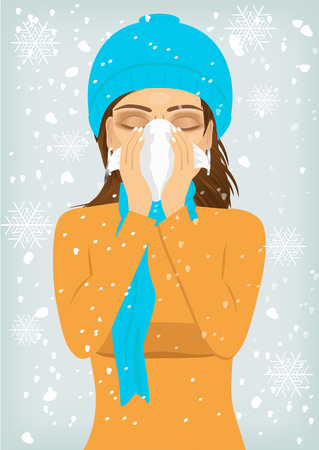 blowing nose: attractive woman wearing a warm knitted cap and scarf suffering influenza and runny nose blowing her nose with a handkerchief
