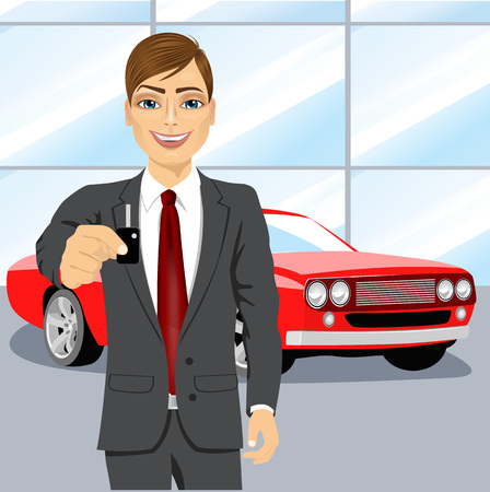 brand new: portrait of young handsome automobile salesman holding the key of a brand new red car into car showroom