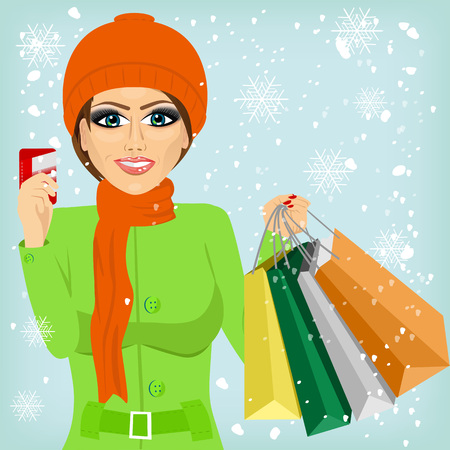 woman credit card: attractive woman shopping on christmas winter day holding credit card and bags