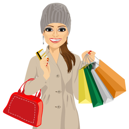 portrait of woman in a winter coat and knitted hat holding multicolored shopping bags, red handbag and her credit card