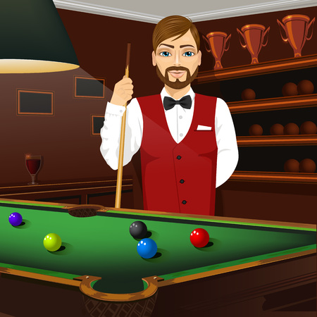 caucasian man: handsome caucasian man in red formal vest holding cue stick standing behind a pool table with colorful billiard balls