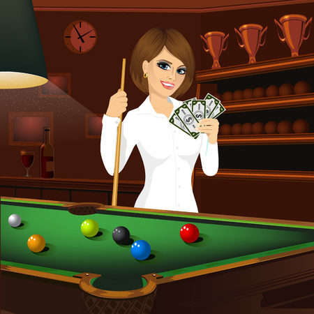 woman holding money: beautiful business woman holding cue stick and fan of money standing behind a pool table with colorful billiard balls