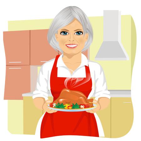 dulce abuela en delantal rojo cocinar el pavo de acción de gracias en la cocina tradicional