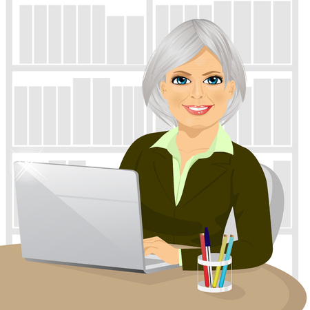 portrait of successful mature businesswoman working typing on her laptop at office