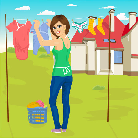 rear view: happy young woman hanging wet clothes out to dry next to family house
