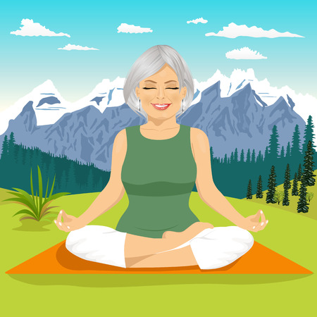 lotus position: portrait of senior woman meditating and exercising yoga lotus position in mountains