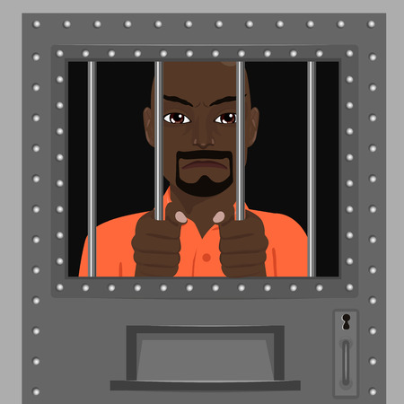 behind bars: african american man looking from behind the bars