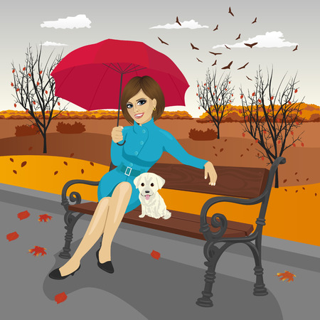 autumn woman: young woman in blue autumn coat holding red umbrella sitting on a bench with labrador puppy in the city park on a rainy day