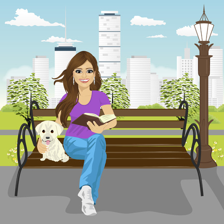 labrador puppy: Young happy woman enjoying freetime in the city park in summer reading book sitting on a bench hugging labrador puppy