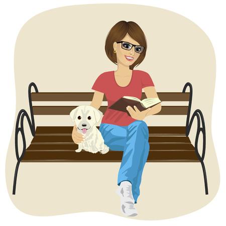 Giovane donna felice godendo tempo libero al di fuori leggendo un libro seduto su una panchina abbracciando cucciolo di labrador