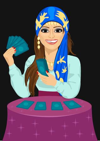 Junge Wahrsagerin in die Zukunft mit Tarot-Karten auf schwarzem Hintergrund prognostiziert