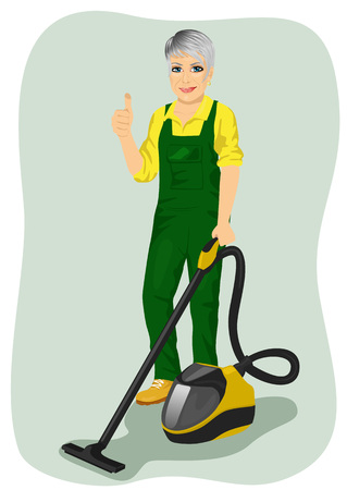 coveralls: Elderly woman in green coveralls posing with a vacuum cleaner and giving thumbs up