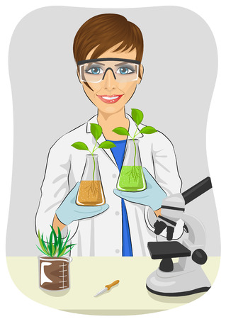 white coat: Young woman biologist in white coat holding two flasks with plants next to microscope in the laboratory