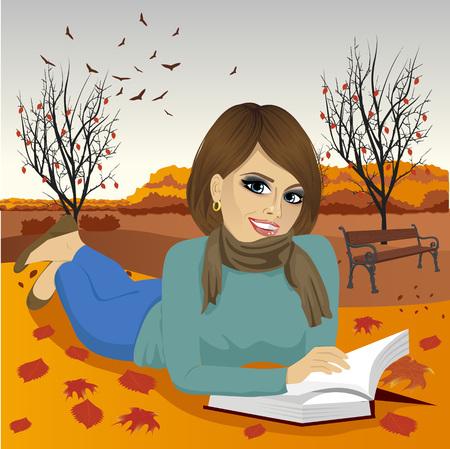 autumn park: Gorgeous brunette woman reading a book in the autumn park