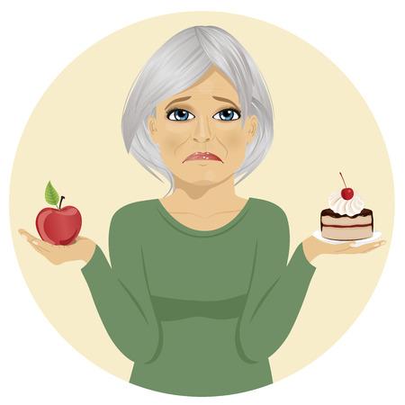 woman eating: Sad senior woman choosing between chocolate layer cake and an apple for dessert
