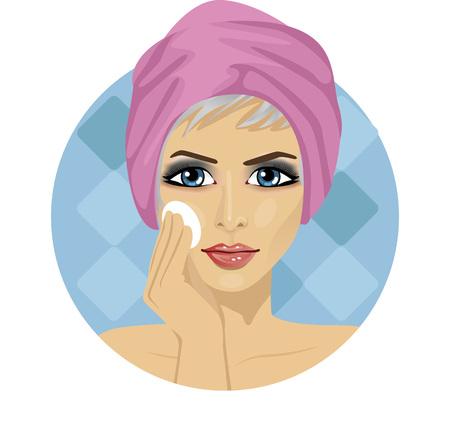 belle femme avec une serviette autour de sa tête de nettoyage son visage avec une éponge