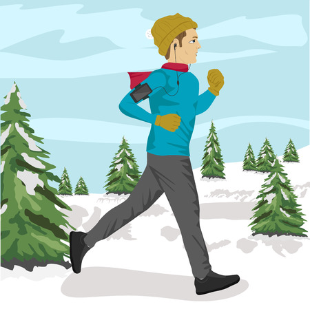 Young sportsman jogging outside in winter park listening to music on smartphone