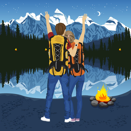 couple back to back: back view of young couple of hikers with hands up enjoying mountain lake at night near capmfire