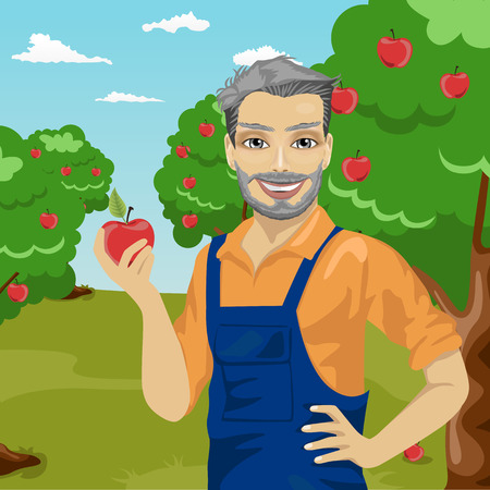 mature farmer man holding an apple in the orchard