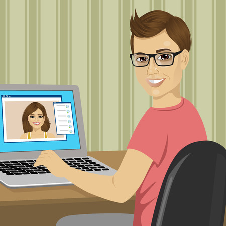 long distance: young nerd boy chatting with his girlfriend with a video call using laptop sending text messages