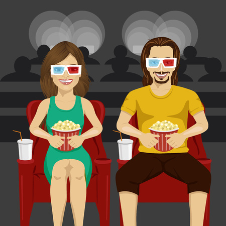 watching 3d: Happy couple sitting in movie theater watching 3D movie, eating popcorn and smiling