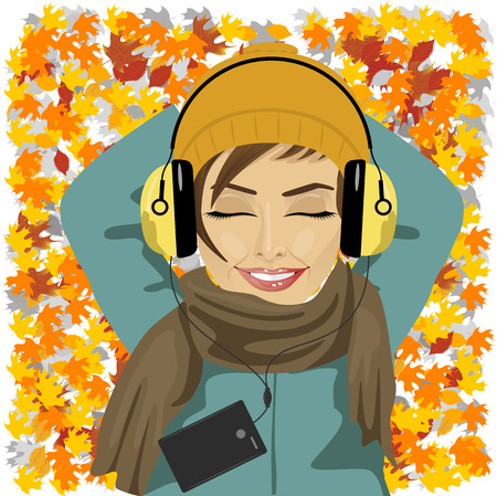 young beautiful woman listening to music lying on autumn leaves floor