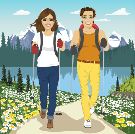 Young couple hiking outdoors with backpacks in summer mountains.