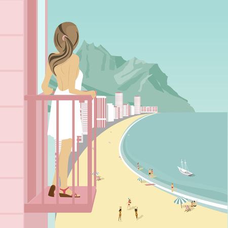hotel building: Young woman stands on balcony of hotel looking at ocean coast with people on beach, mountains and buildings along road