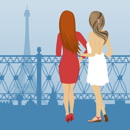 Rear view of two women standing on embankment and look at the Eiffel Tower in Paris