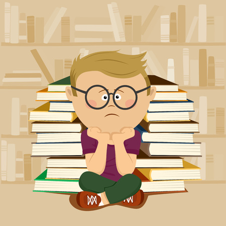 Unhappy nerd boy sitting in front of a stack of books and bookshelf in school library