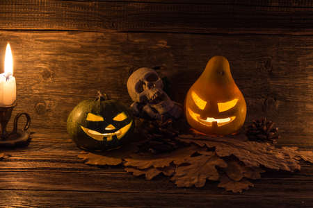 Halloween symbol pumpkin smiling jack-o-lantern and burning candle on dark wooden background