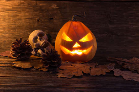 Pumpkin with glowing eyes and a skull on wooden background. Sinister halloween.