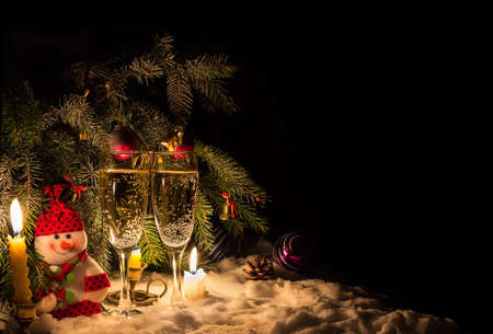flickering: Symbols of New Year - shampane, snowman and candles. Dark background with copy-space.