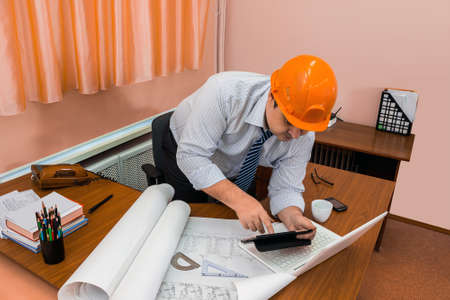 carefully: Architect is working on a sketch of the architectural plan at the table in the office
