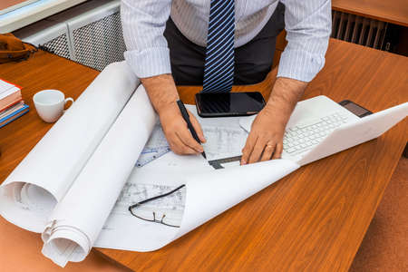 carefully: Architect man working with  blueprints. Engineer in workplace with architectural plan.
