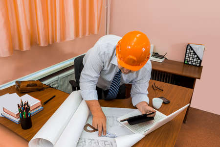 carefully: Engineer in helmet working with drawings. Check the drawing. Adjustment of the project. Stock Photo