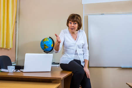 teaching material: A female teacher in a classroom holds a lesson. Explains the new teaching material. Teacher at work.