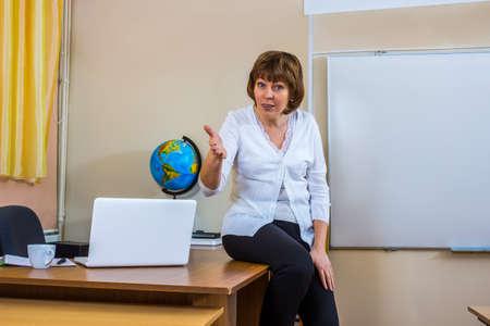 explains: A female teacher in a classroom holds a lesson. Explains the new teaching material. Teacher at work.