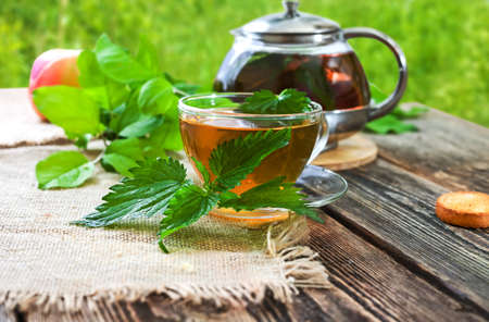 Healing tea with nettle. Tea in a glass cup on a wooden table. Folk remedy. The source of vitamins. Stock Photo