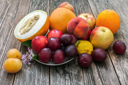 A pile of ripe fruit on the table. Melon, apples, plums, lemon, peaches, apricots and grapefruit on a wooden table. Side view.