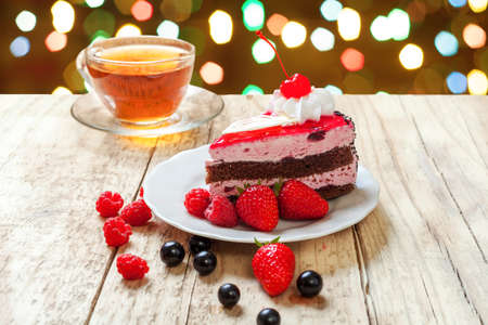 A festive cake with cherries and berries against a bright colored bokeh. Festive treat for your birthday or Christmas.