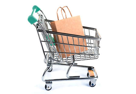 Shopping trolley with paper bags. Concept: shopping in the supermarket. White background. Side view.