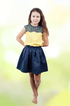little girl in a yellow blouse on a bokeh background on a summer day