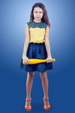 little girl in a yellow blouse with a yellow toy baseball bat on a blue background