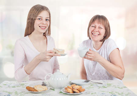 Two friends drink tea and talk. They laugh and hold the cups. Archivio Fotografico